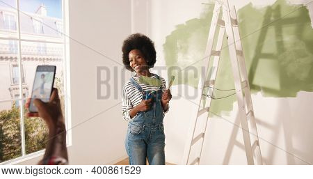 African American Lovely Husband Taking Photos Of Beautiful Happy Wife In Room Doing Renovation In Ho