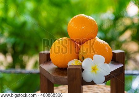 Oranges Close-up On A Wooden Stand Decorated With Frangipani Flowers, Vegan And Vegetarian Products,