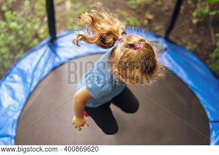 Little Girl Jumping On A Trampoline On A Summer Day.