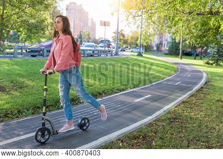 Girl In Summer In City Rides A Scooter, In Casual Clothes Jeans And A Pink Jacket, Free Space For A