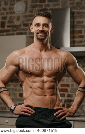 A Muscular Man With A Beard Is Posing In His Apartment. The Athletic Guy With Tattoos On His Forearm