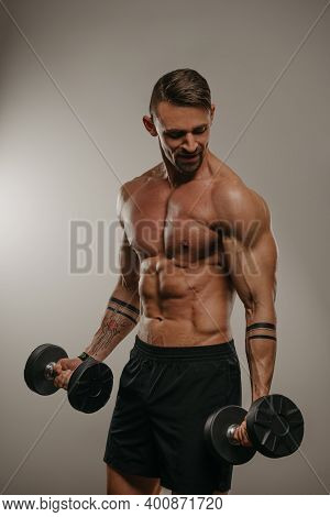 A Muscular Man With A Beard Is Doing Bicep Curls With Dumbbells. An Athletic Guy Is Demonstrating Hi