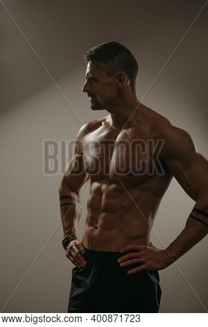 A High Contrast Photo Of A Muscular Man With A Beard Who Is Posing. The Athletic Guy Is Demonstratin