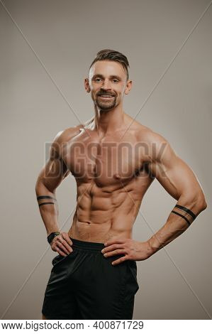 A Smiling Muscular Man With A Beard Is Posing. The Athletic Guy Is Demonstrating His Sporty Physique