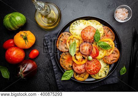 Ripe Fresh Colorful Tomatoes Salad With Olive Oil And Basil Leaves On Black Background, Top View