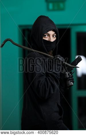 Thief Broke Into The Apartment. House Robbery By Woman In A Black Jacket And Black Mask Black Gun An