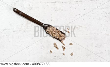 Peeled Sunflower Seeds In Small Wooden Scoop, Placed On White Stone Like Board, View From Above