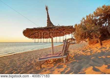Two Empty Wooden Sunbeds Facing The Sunset, Sea In Background, Straw Sun Shade Above, Image Illustra