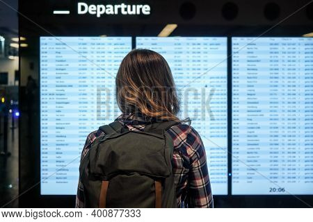 Young Woman With Green Backpack And Shirt Looking At Departure Board Screen At The Airport, View Fro