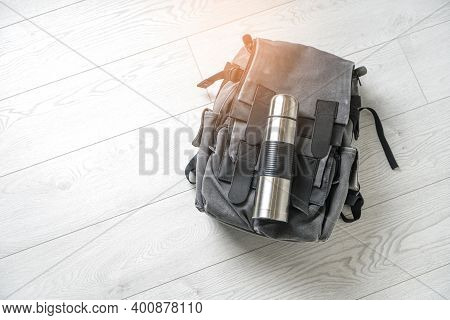 Preparing For Hiking Adventure. Outing Into Nature Concept. Background With Backpack And Thermos Lyi