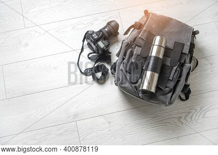 Preparing For Hiking Adventure. Outing Into Nature Concept. Background With Backpack, Thermos And Ph