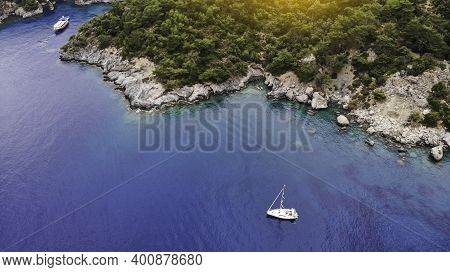 Aerial View Of Yacht Beside The Coastline Of Mediterranean Sea. Mediterranean Nature Top View From D