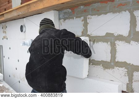 A Building Contractor Is Installing An External Solid Wall Insulation Fixing Insulating Polystyrene