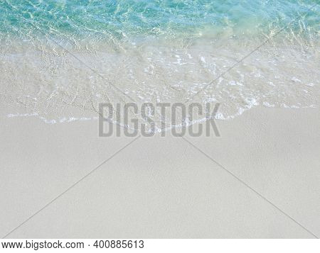 Foamy Waves On A Sandy Beach With Blue Sea Water At A Tropical Beach