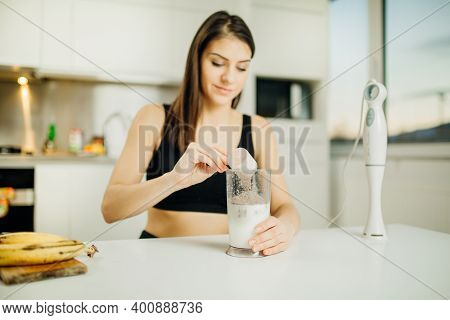 Woman With Immersion Blender Making Banana Chocolate Protein Powder Milkshake Smoothie. Adding A Sco