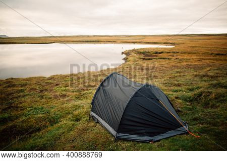 Setting Up Tent. Camping Outside On A Beautiful Meadow Near The Lake. Road Trip Camping In Iceland.