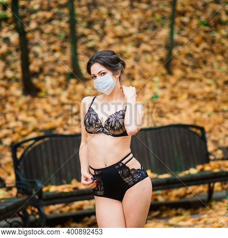 Fashion Portrait Of Sexy Woman In Face Mask And Bodysuit In Autumn Park. Pandemic, Coronavirus