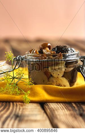 Marinated Mushrooms In Glass Jar, Herbs And On Wooden Table. Canned Vegetatian Dish. Natural Light.