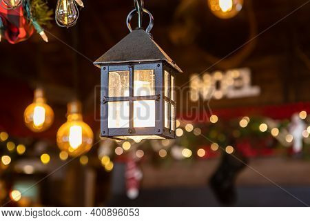 Selective Focus Of Beautiful Little Hut Shaped Lamp With Illuminated Bulb And Noel Text Written In B