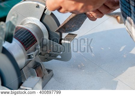 Close-up Of Mens Hands Sharpening An Axe On An Electric Sharpener. Repair Of Home Tools With Your Ow