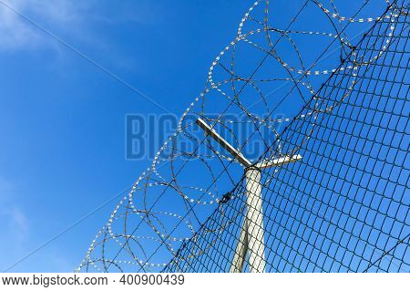 Barbed Wire Against A Blue Sky. Prison Concept. Entry Order. Military Base. Detail Of New Fence With