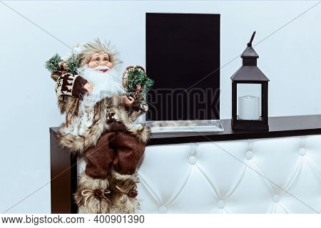 A Toy Silver Deer Stands On The Table Against The Background Of A Christmas Tree, Balloons And Masks