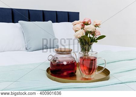 White Bedside Table Near The Bed, Against A White Wall. There Are Objects, A Vase With Green Grass,