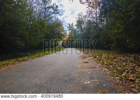 Augusta, Ga Usa - 12 12 20: Augusta Canal Trail Empty Paved Trail With Fall Foliage And Leaves And S