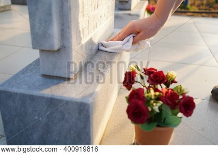 Cleaning Cemetery. A Womans Hand Washes Grey Monument At The Grave With Rag