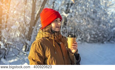 Young Woman Is Drinking Hot Coffee On A Frosty Winter Sunny Day Outdoors In The Forest