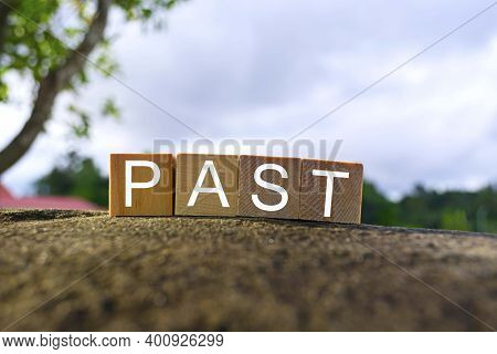 Past Text On Wooden Block On Top Of Big Stone With Blurred Sky Background