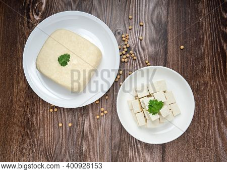 Whole Fresh Tofu In White Plate And Diced Tofu In Dish On Wood Background. Full Depth Of Field. Vega