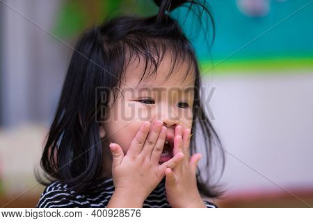 Portrait Of One Child Little Girl Flick The Candy Crumb That Is Stuck On Her Face. The Girl Eats Slo