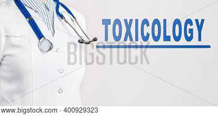 Word - Toxicology On A White Background. Nearby Is A Doctor In White Coat And Stethoscope. Medical C