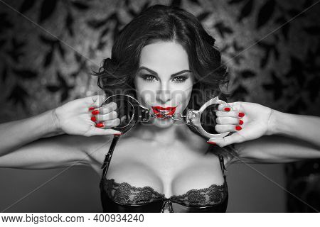 Sexy Woman Holding Handcuffs In Nightclub, Red Lips, Black And White Selective Coloring, Bdsm