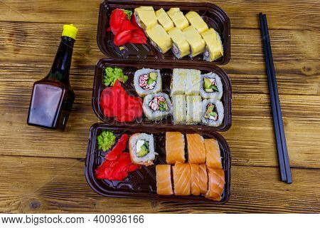 Set Of Sushi Rolls In Plastic Boxes, Soy Sauce And Chopsticks On Wooden Table. Top View. Sushi For T