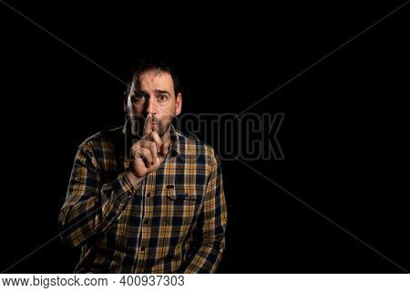 Handsome Man Giving Shhh Hush, Hush, Secret Isolated On Black Studio Background. Gesture Of Finger L