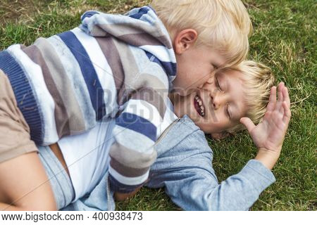 Two Brothers Have Fun Playing On The Lawn