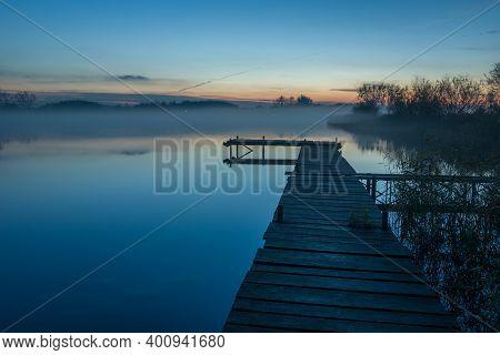 Footbridge On The Lake And Evening Fog
