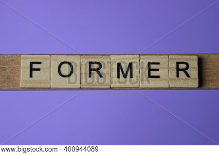 Gray Word Former In Small Square Wooden Letters With Black Font On A Lilac Background