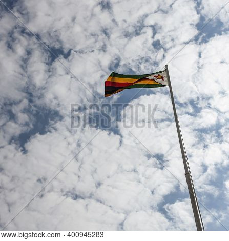 National Flag Of Zimbabwe On Flagpole In The Blue Sky. Flag Of The Republic Of Zimbabwe Against The