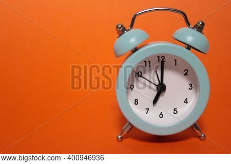 A Small Blue Alarm Clock On An Orange Background, On The Dial Of Which 07: 00. Morning Rise To Work.