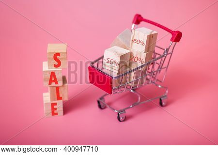 Miniature Shopping Cart And Wooden Blocks With Sale Lettering, Isolated Pink Background.