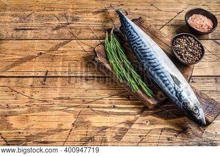 Raw Saltwater Fish Mackerel On A Wooden Cutting Board With A Thyme. Wooden Background. Top View. Cop