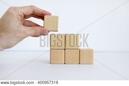 Symbol Of Building Success Foundation. Men Hand Put Wooden Cube On The Pyramid From Wooden Blocks. B