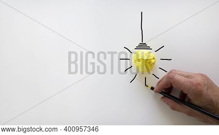 Idea And Innovation Concept Image. Male Hand With Black Pencil. Yellow Light Bulb Icon. Beautiful Wh