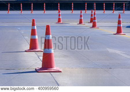 Orange Traffic Cones With Plastic Warning Poles On Entrance Way That Connect To Main Road For Conven