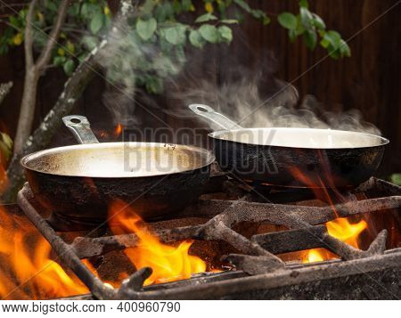 Pans On The Grill On The Grill On A Bright Fire. A Man Cooks On A Fire In Pans.