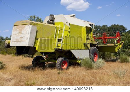 rear view of combine harvester on the land poster