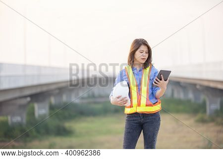 Woman Engineer With White Security Helmet Holding Tablet Standing On Construction Site